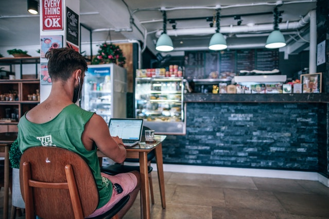 Man working on laptop in cafe